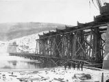 Five men, possibly including Frederick Mears at left, posing near Tanana River railway bridge...