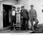 Aleut family, three men and boy, posed on porch of house, Saint Paul Island, 1896