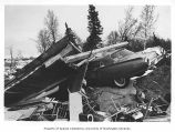 Earthquake damage showing car trapped under collapsed building, vicinity of Anchorage, 1964