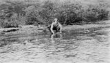 Man panning for gold on riverbank, vicinity of Nome, 1903-1920