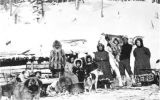 Eskimo family and sled dogs in front of snow-covered structure near forest, vicinity of Nome,...