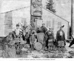 Tlingit men and boy in traditional costumes standing in front of totem pole, Fort Tongass, Dec....