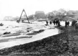 Ice breaking up along Snake River, with equipment, men and buildings along shore, Nome,  1916