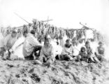 Kauwerak Eskimo family sitting on sand in front of drying racks filled with fish, vicinity of...