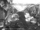 Interior of tunnel of snow shelter with furs, snowshoes, dried fish and other provisions, Seward...