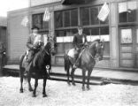 Two men on horseback with sashes and ribbons in front of building flying American flags, Nome, ca....