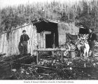Two men and a dog outside cabin, Eldorado mine, ca. 1898