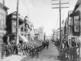 Decoration Day parade of soldiers on board-planked street (probably Front Street), Nome, Alaska,...