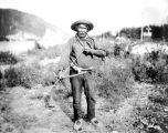 Native man with what appears to be a bow and arrow near Fairbanks, Alaska, ca. 1915.
