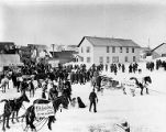 Crowd with horse drawn sleds and wagons with political banners on election day, Nome, Alaska, 1902