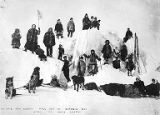 Group of men, women, and children with dogsled team and skiis posed on ice hummock near Nome,...