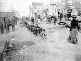 Dog team pulling wagon on Front Street, Nome, Alaska, circa 1902