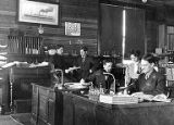 Four men and one woman working in the John J. Sesnon Company offices, Nome, Alaska, 1908