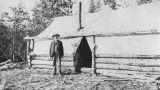 Chesley outside tent at Tramway Camp, likely Conrad, Yukon Territory, October 1905