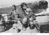 Eskimo woman nursing a small child, location unknown, ca. 1909