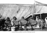 Four Eskimo men with drums seated in front of shelter, location unknown, n.d.