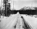 Chitina-Fairbanks Road in snow with Mt. Wrangell possibly in background, possibly near McCarthy,...
