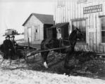 Two men in horse-drawn sleigh in front of roadhouse, Nome, Alaska, circa 1905