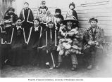 Group of Tlingit in ceremonial dress, button blankets, beaded jacket, painted hat, and carved...