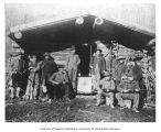 Men with rifles in front of a cabin, Eldorado Mine, Great Bear Lake, ca. 1897