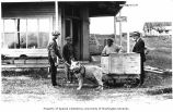 Four men, two of them African American, with dog harnassed to wagon outside store, Eagle, n.d.