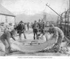 Dock scene with men working in foreground and boats visible in background and to right, Seward,...