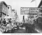 Crowded Front Street scene with men and horse-drawn carts, Nome City Drug Store and other business...