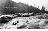 Three people in a canoe, one with hat in upraised hand, shooting Whitehorse Rapids, near...