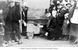 George Lawler sealing box in the cornerstone of the new Public School with crowd watching, Juneau,...
