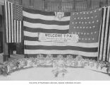 Welcome T.P.A. flag hung over tables with fruit baskets, Alaska-Yukon-Pacific-Exposition, Seattle,...