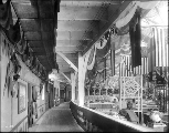 Corridor of exhibits inside the Manufactures Building showing displays for Otis Elevators and the...