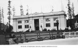 King County Building showing an unidentified man reading on a bench in foreground,...