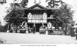 Hoo Hoo House with unidentified man standing in front, Alaska-Yukon-Pacific-Exposition, Seattle,...