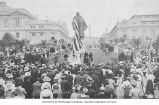George Washington statue covered with draped American flag and surrounded by a crowd of visitors,...