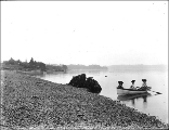 Three women in a rowboat in water at the edge of a beach, unidentified location, probably...