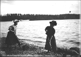 Two women digging clams with pitchforks on the beach in Burton, Vashon Island, Washington, ca. 1905