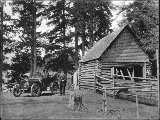 Three men with automobile parked next to log cabin with corral, probably Washington state, ca....