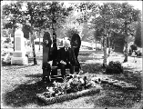 Older man seated next to gravesite covered with flowers, Oregon, ca. 1913.