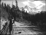 Man with camera and tripod photographing views in Mount Rainier National Park, Washington, ca....