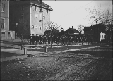 Military cadets or soldiers engaged in drill on sidewalk in front of unidentified building,...