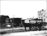Two men with horse and cart in front of the Gilstrap Dental Palace and The Hughes Laundry,...