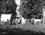 Ezra Meeker's camp with covered wagon, tent, and horses in yard, Oregon, ca. 1913