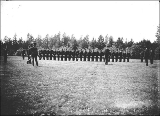 Military cadets or soldiers performing drill or standing in review, probably Washington State, ca....
