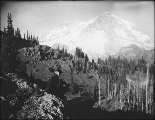 Man seated on rock holding Kodak camera, Indian Henry's Hunting Ground, Mount Rainier National...