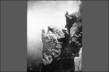 Hiker sitting on top of Cowlitz Rocks, Mount Rainier National Park, Washington, ca. 1913