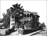 Two women and a girl posed outside of house with balconies. Palm trees in front lawn.