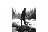 Elcaine Longmire with rifle standing on large boulder in riverbed, Mount Rainier National Park,...