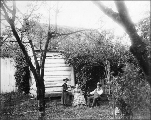 Homesteaders seated outside in garden surrounding house, probably Washington state, ca. 1905.