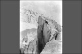 Man peering into crevasse in Paradise Glacier, Mount Rainier National Park, Washington, 1913.