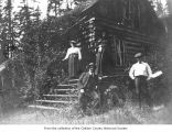 The Hotel at Lake Sutherland showing two men and two women near stairs outside a cabin, Clallam...